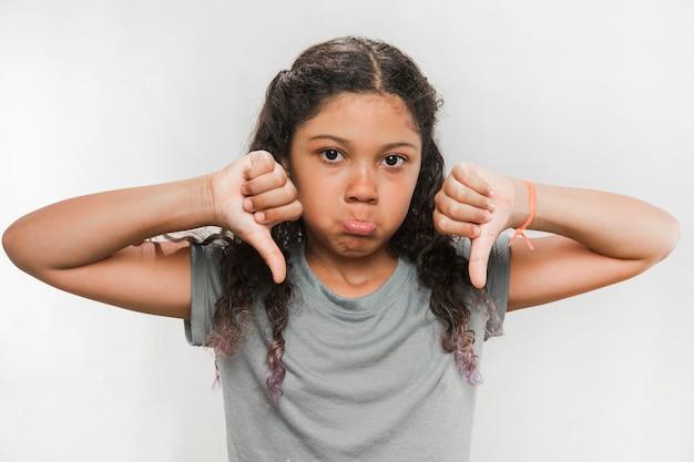 Retrato de uma menina chateada gesticulando polegares para baixo