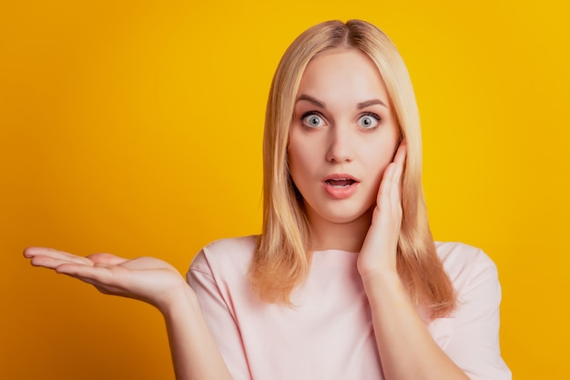 Retrato de uma menina chocada e animada conselheira segurando a palma da mão na cópia em fundo amarelo