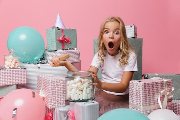 Retrato de uma menina chocada em um chapéu de aniversário
