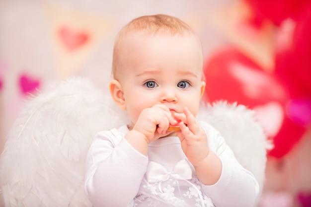 Retrato de uma menina com asas de penas brancas comendo biscoitos em forma de coração