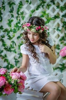 Retrato de uma menina com cabelo comprido e uma coroa de flores frescas na cabeça dela. sessão de fotos da primavera.