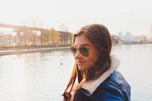 Retrato de uma menina com cabelos compridos e óculos em um fundo de um lago, refletindo as nuvens.
