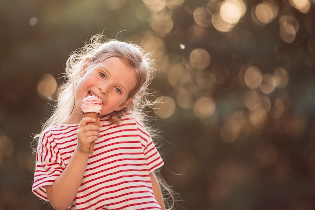 Retrato de uma menina com cabelos loiros ondulados, tomando sorvete, aproveitando o sol poente