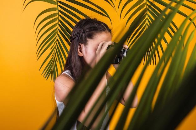 Retrato de uma menina com câmera em um fundo amarelo.