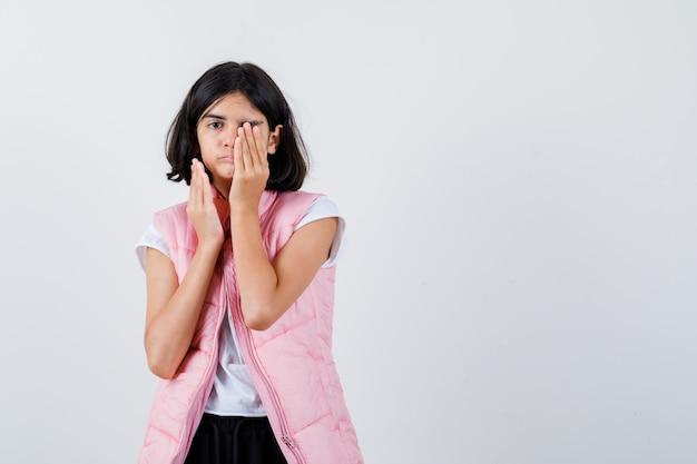 Retrato de uma menina com camiseta branca e colete bufê cobrindo os olhos