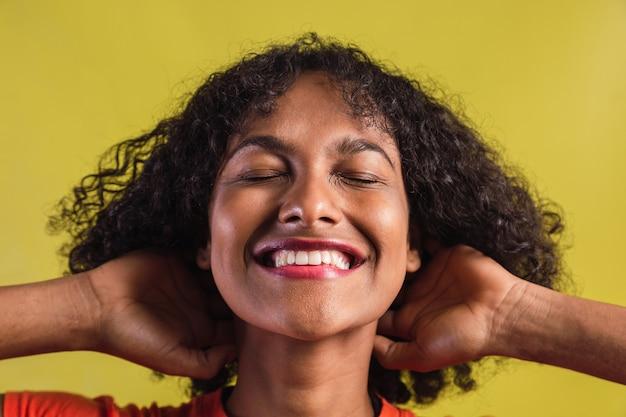 Retrato de uma menina com estilo afro, sorrindo com os olhos fechados.