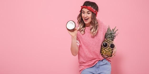 Retrato de uma menina com frutas em uma parede rosa