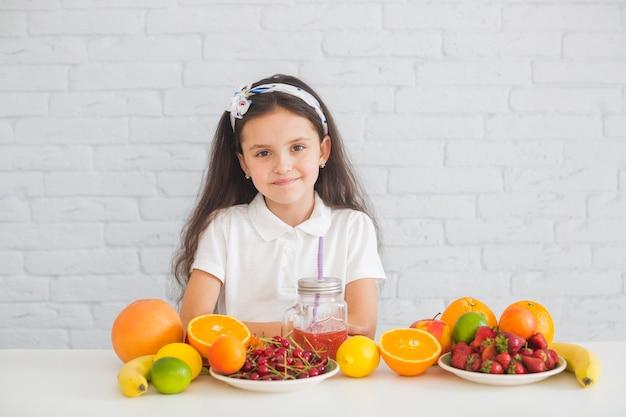 Retrato de uma menina com frutas maduras coloridas na mesa