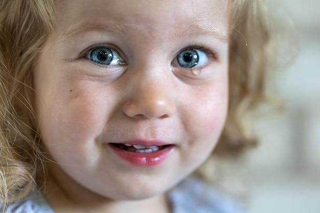 Retrato de uma menina com grandes olhos azuis, olhos marejados de lágrimas de uma criança.