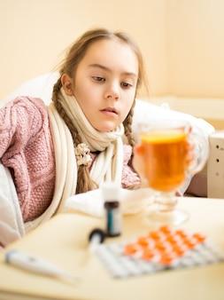 Retrato de uma menina com gripe deitada na cama e olhando para uma xícara de chá