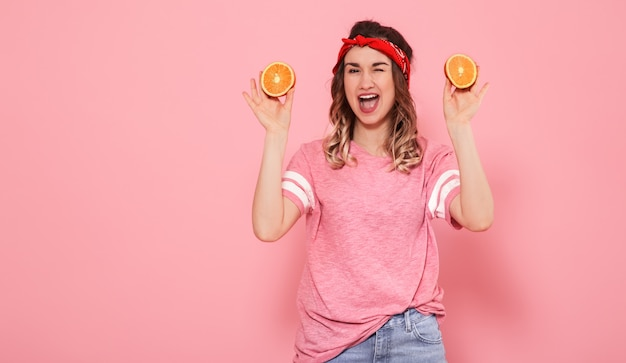 Retrato de uma menina com laranjas na mão, em uma parede rosa