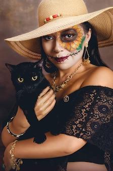 Retrato de uma menina com maquiagem catrina e um gato preto nos braços