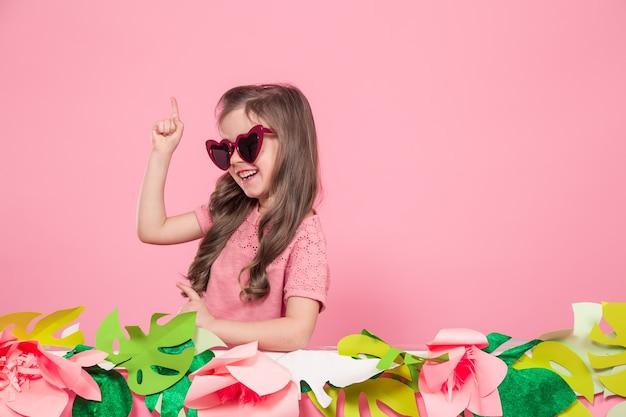 Retrato de uma menina com óculos escuros em uma parede rosa