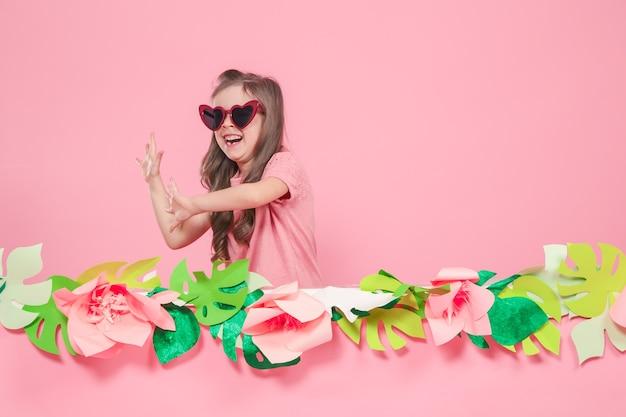 Retrato de uma menina com óculos escuros em uma parede rosa Foto gratuita