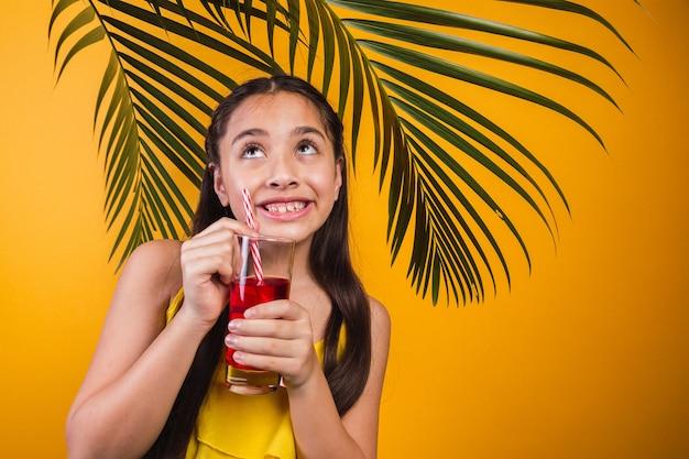 Retrato de uma menina com olhar travesso, segurando um suco de fruta em fundo amarelo.