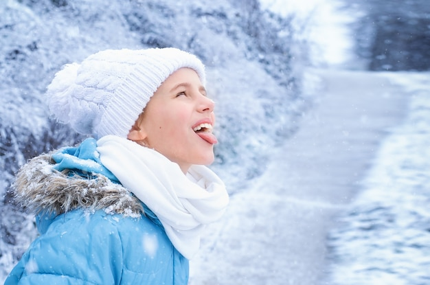 Retrato de uma menina com roupas de inverno azul, pegando flocos de neve com a língua no parque.