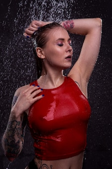 Retrato de uma menina com seios lindos em uma camiseta vermelha molhada, tomando banho com brilhantes gotas de água caindo.