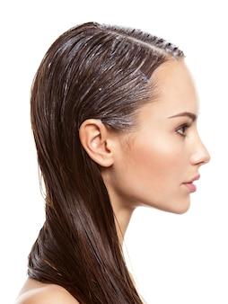 Retrato de uma menina com tinta aplicada para cabelos na parede branca