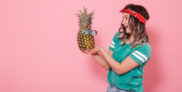 Retrato de uma menina com um abacaxi em uma parede rosa