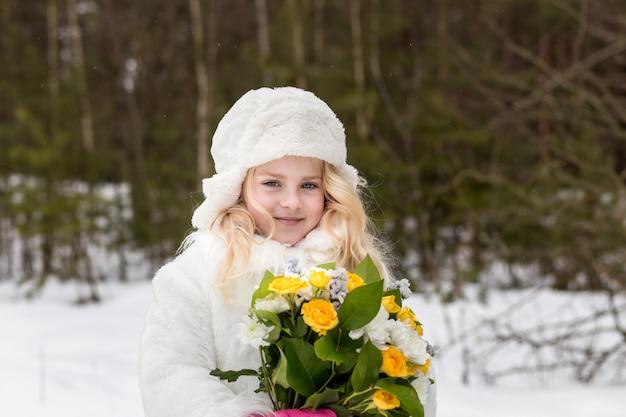 Retrato de uma menina com um buquê de flores na floresta no inverno