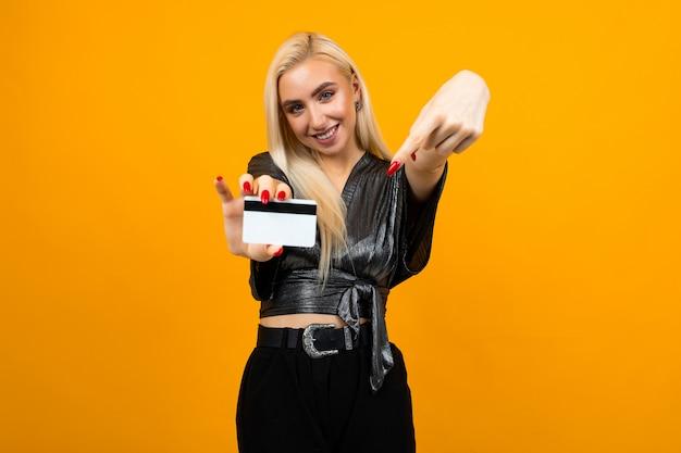 Retrato de uma menina com um cartão com uma maquete para fazer compras em um fundo amarelo