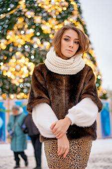 Retrato de uma menina com um casaco de pele no fundo de uma árvore de natal.