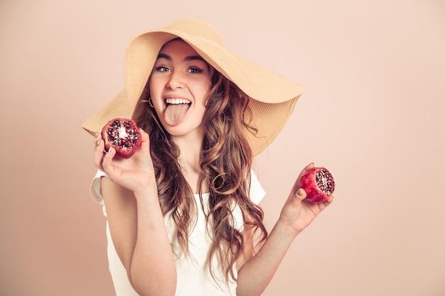 Retrato de uma menina com um chapéu de verão com frutas em uma parede colorida