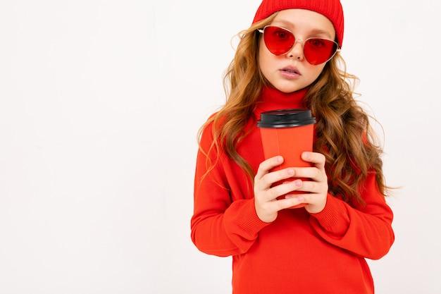 Retrato de uma menina com um chapéu vermelho e óculos de sol com um copo