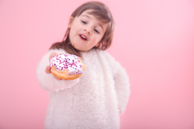 Retrato de uma menina com um donut nas mãos dela
