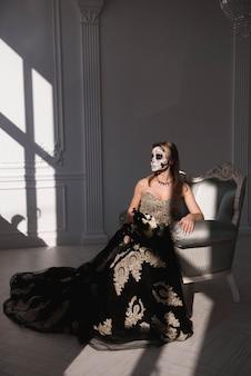 Retrato de uma menina com um homem morto de maquiagem no halloween.