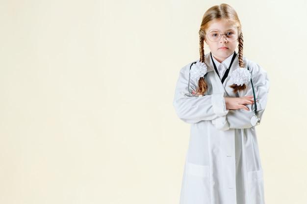 Retrato de uma menina com um jaleco branco com óculos, documentos e um estetoscópio que olha para a câmera e sorri