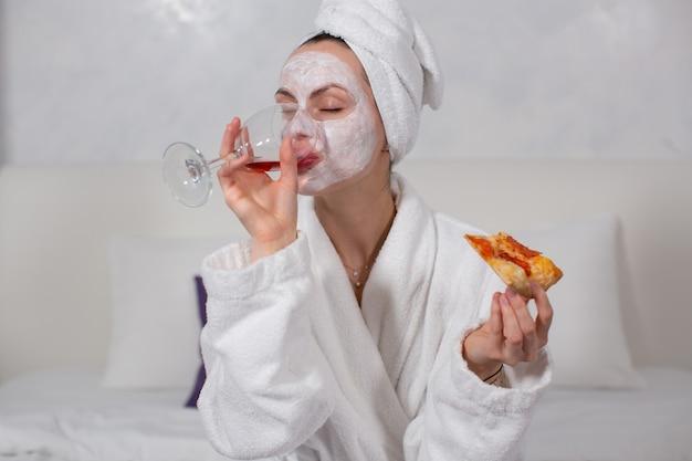 Retrato de uma menina com um manto branco e uma máscara facial hidratante que bebe vinho tinto em um copo e come pizza enquanto está sentada em seu quarto de hotel foto de alta qualidade