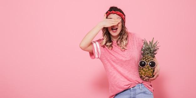 Retrato de uma menina com um olho fechado em um fundo rosa