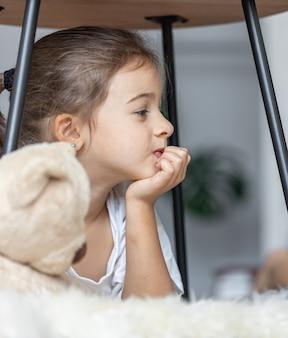 Retrato de uma menina com um ursinho de pelúcia deitado no chão da sala.