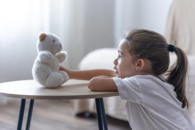 Retrato de uma menina com um ursinho de pelúcia em um fundo desfocado no interior da sala.