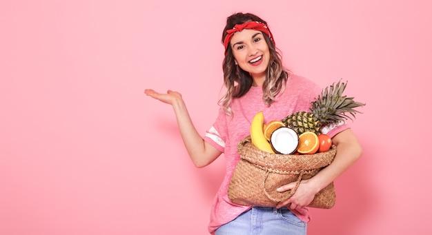 Retrato de uma menina com uma bolsa com frutas isoladas em uma parede rosa