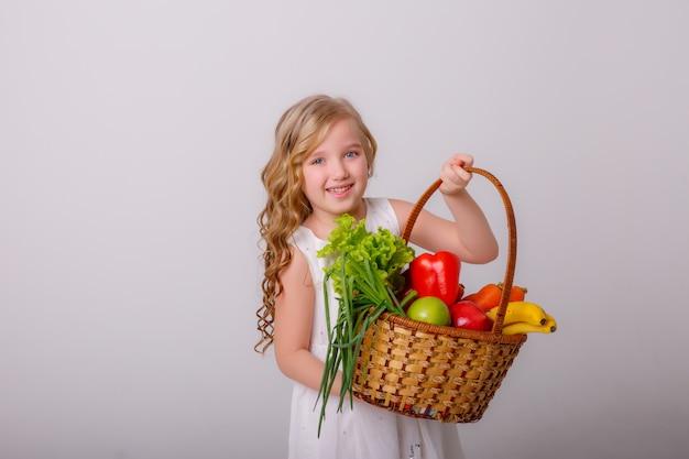 Retrato de uma menina com uma cesta de legumes nas mãos dela, sorrindo