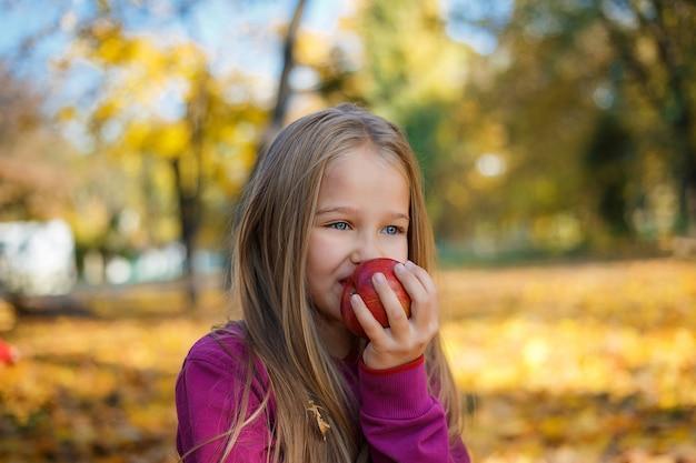 Retrato de uma menina com uma maçã na mão no parque outono