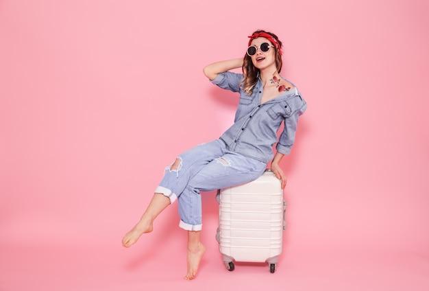 Retrato de uma menina com uma mala em uma parede rosa