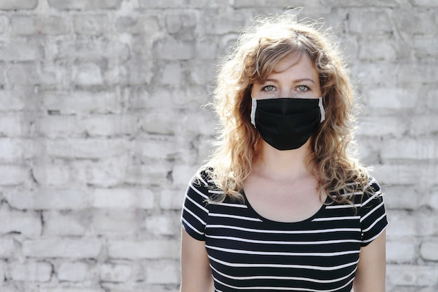 Retrato de uma menina com uma máscara protetora em uma parede de tijolos brancos ao fundo