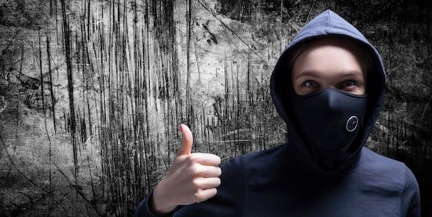 Retrato de uma menina com uma máscara protetora, mostrando um polegar para cima