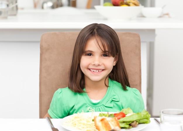 Retrato de uma menina comendo macarrão e salada