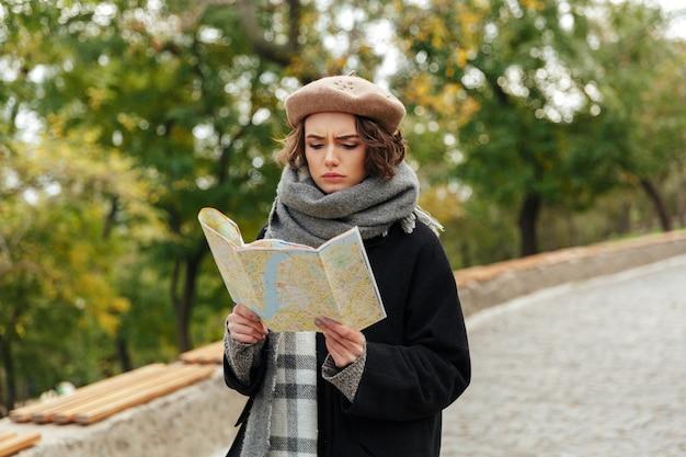 Retrato de uma menina concentrada, vestida com roupas de outono