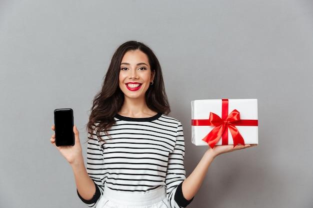 Retrato de uma menina confiante, mostrando o telefone móvel de tela em branco