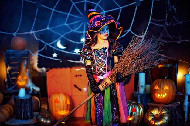 Retrato de uma menina criança bonitinha em uma fantasia de bruxa com vassoura mágica.