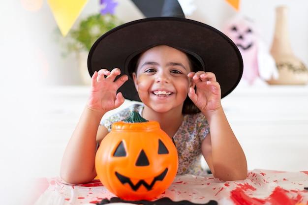 Retrato de uma menina criança caucasiana sorridente ao lado de abóbora de halloween e outros elementos decorativos de celebração.
