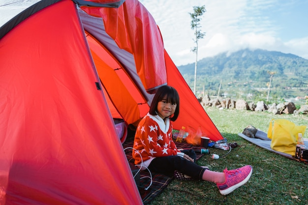 Retrato de uma menina curtindo o acampamento com a bela paisagem da colina