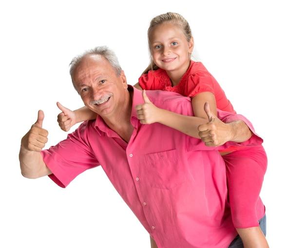 Retrato de uma menina curtindo um passeio nas costas com o avô em uma parede branca