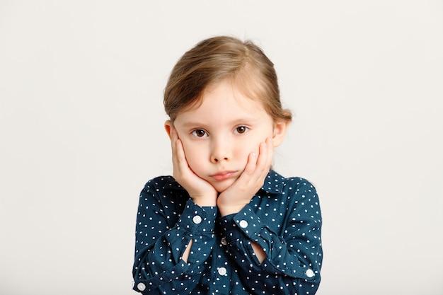 Retrato de uma menina de 46 anos, ofendida, sombria e zangada, usando um vestido azul com bolinhas