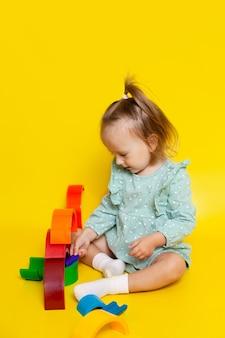 Retrato de uma menina de bebê fofo com olhos azuis em um fundo amarelo, brincando com um designer de arco-íris. jogos e brinquedos educativos. ensinando a criança. cor. um lugar para texto. foto de alta qualidade